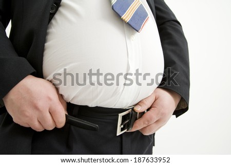 An obese man in a suit struggles to fasten his belt. - stock photo