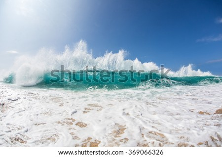 An ocean shorebreak in front view. Big beautiful green blue wave splashing with backwave and ready to break out. White foam sliding over sand. Bright sun shining on blue sky. - stock photo