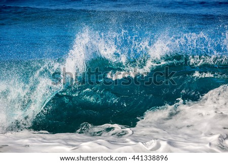 An ocean shorebreak in front view. Big beautiful green blue wave splashing with backwave and ready to break out. White foam sliding over sand. Bright sun shining on blue sky.