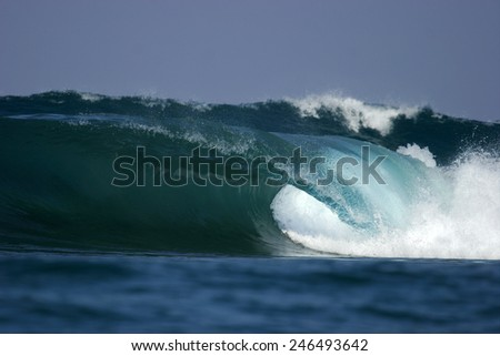 An ocean wave breaks over a shallow reef in Mozambique. - stock photo