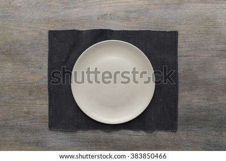 An off-white plate on a black placemat on a wooden table - stock photo