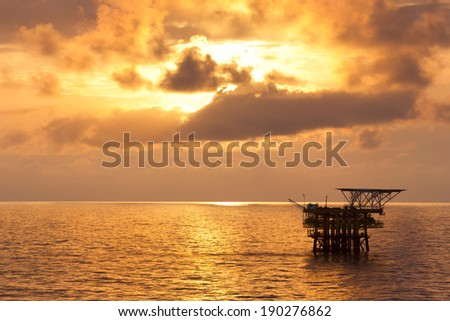 An offshore oil platform at sunrise - stock photo