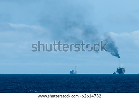 An offshore oil rig burning gas at the horizon.  Coast of Brazil - stock photo