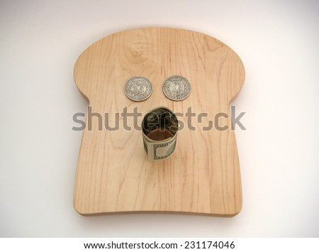 An Oh Face Formed With Two Silver US Morgan Dollars For The Eyes And A United States Hundred Dollar Note For The Mouth Resting On A Bread Shaped Cutting Board Over White With Slight Vignetting. - stock photo