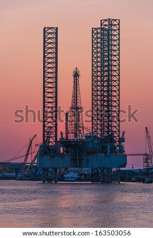 An oil drilling platform is under construction at sunset in Galveston, Texas.
