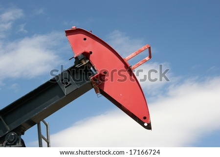 An oil drilling pump jack with a red head