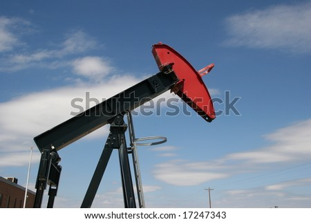 An oil drilling pumpjack with a red head