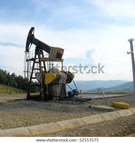 An oil pump jack in the middle of a mountain landscape