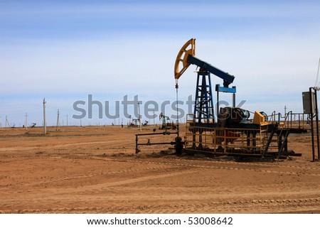 An oil pump jack on blue sky. - stock photo
