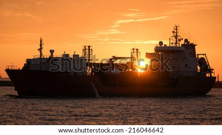 An Oil Tanker Entering Kaohsiung Port Under Sunset, With Sunlight Shine Through the Ship. - stock photo