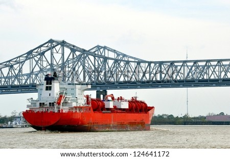 An Oil Tanker Ship Passing Beneath The Greater New Orleans Bridge On The Mississippi River - stock photo
