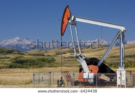 An oil well pump in the foothills of Alberta with the Rocky Mountains in the background.