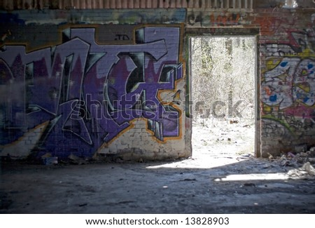 An old abandoned area that has been converted to a paint ball course. Every inch is covered with graffiti. - stock photo