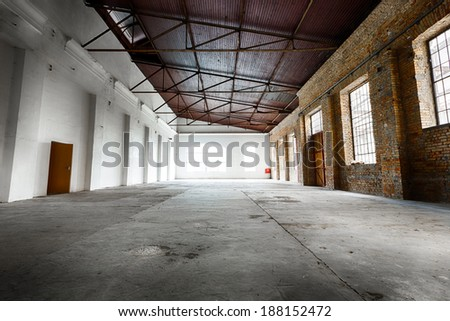 an old abandoned empty warehouse interior - stock photo
