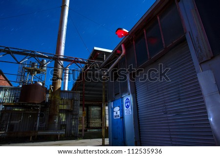 An old abandoned factory scene at night. Long exposure light painting - stock photo