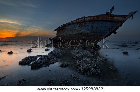 An old abandoned fishing boat stranded on a beech. - stock photo