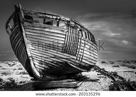 An old abandoned fishing boat stranded on a beech in black and white. Old fishing boat. - stock photo