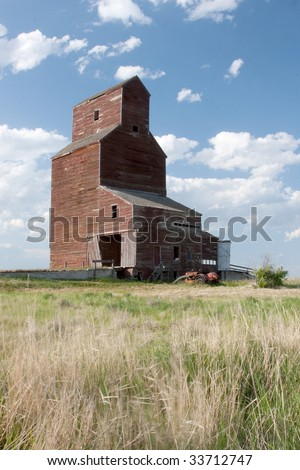 An old abandoned grain elevator on the Canadian prairies.  Trademarked logos have been removed. - stock photo