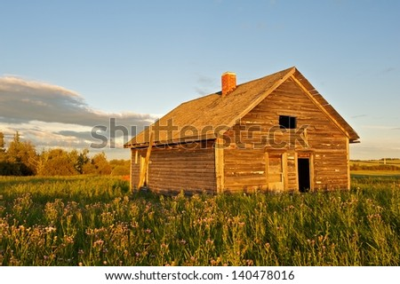 An old abandoned house at sunset - stock photo