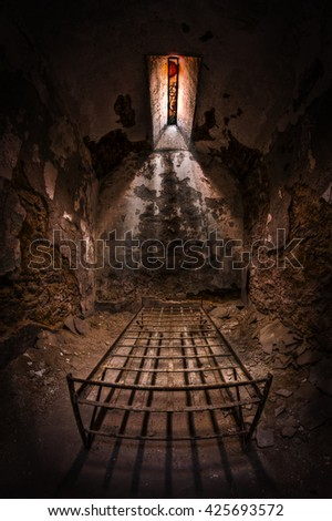 An old abandoned room with a metal bed and a stained glass window - stock photo