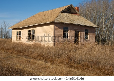 An old abandoned rural school in fall  - stock photo