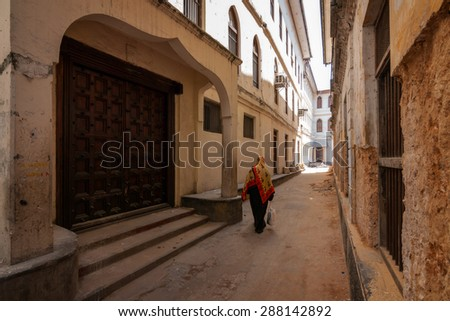 an old african arab street scene in stonetown zanzibar showing a back alleyway between old rustic buildings - stock photo