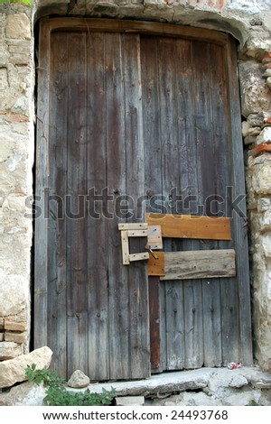 An old and aged wooden door and bolt action locking mechanism.
