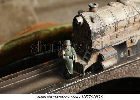 An old and dirty plastic train toy model and miniature plastic military figure model on bridge model scenery represent the train toy  for hobby and collection concept related idea.