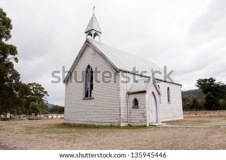An old and weathered wooden church stand in the countryside with a nearby cemetery