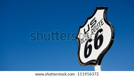 An old, antique, nostalgic route 66 sign in front of blue sky - stock photo