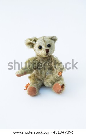 An old, antique teddy bear with holes and his stuffing coming out. A simple white, vertical background. Cute and adorable for a variety of ideas and concepts.  - stock photo