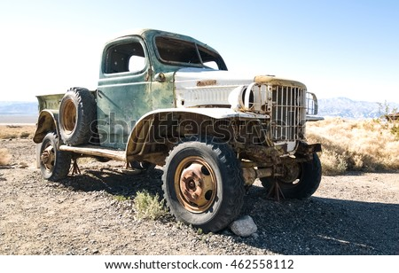 An old automobile retired and rusting away in a western ghost town.
