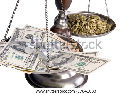 An old balance scale.  Gold nuggets in the rear and US currency and financial dice in the front.  Conceptual image for international finance, money markets, global economy, etc.  Isolated on white. - stock photo