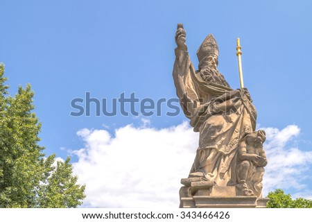 An old baroque statue of St Augustine on the Charles' bridge in Prague, holding a book and a burning heart, with an angel attempting to pour the sea out of a sea-shell - stock photo