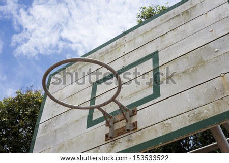 An old basketball backboard and rim under blue sky