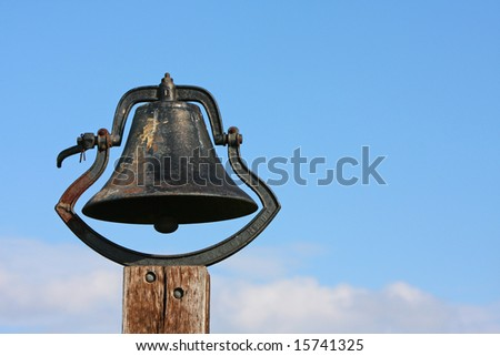 An old bell on a post next to a church and grade school.