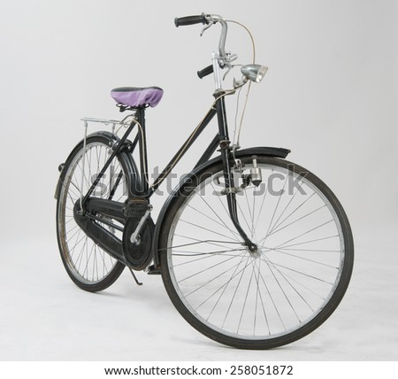 An old bicycle against a plain background - stock photo