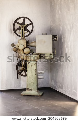 an old big cinema projector in the hallway of a theater - stock photo