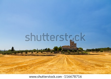 An old big country house surrounded by golden fields in Tuscany, Italy - stock photo