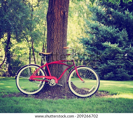 an old bike leaning against a big tree toned with a retro vintage instagram filter  - stock photo