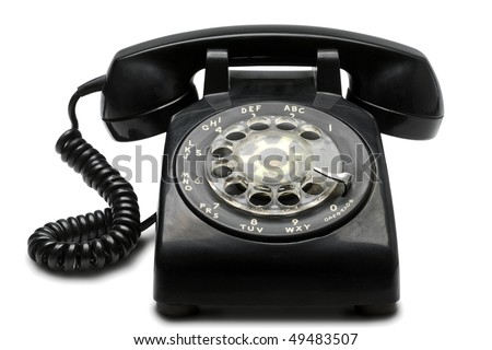 an old black rotary phone on white with clipping path - stock photo