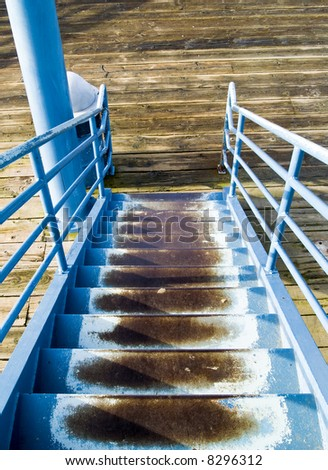 An old blue staircase on a pier leading to a lookout tower.