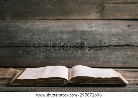 An old book on an old wooden background - stock photo