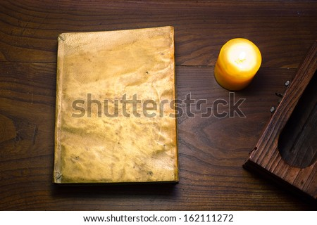 An old book with leather covers illuminated by a candle on a wooden table - stock photo