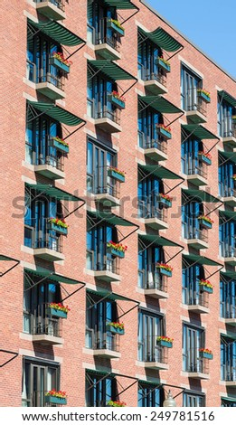 An old brick building in Boston with many balconies and geraniums in window boxes - stock photo