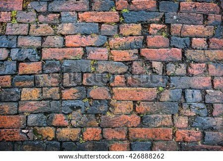 An old brick cobbled road surface.