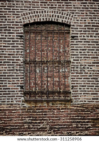 An old brick wall and window with iron bars.