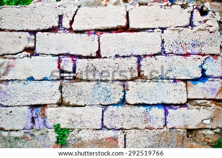 An old brick wall with traces of colorful paint - stock photo