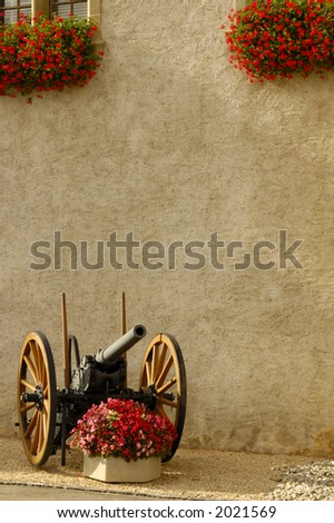 An old cannon outside a castle in Switzerland, guarding a tub of begonias. Geraniums on the window ledges above.