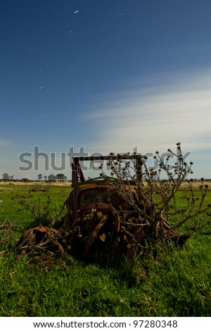 An old car rusting away in a field, Taken using long exposure at night. - stock photo